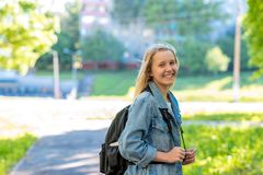 A teenage girl. In the summer in park. Behind the backpack. Concept Soon to school. Free space for text. Emotion smiles. A teenage girl. In the summer in the stock image