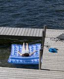 Teenage Girl Sunbathing on Raft at Lake. Young adolescent girl (14 yrs. old) lying face down on raft in very strong sun at lake.  She is tethered to a wooden Royalty Free Stock Image