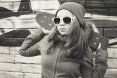 Teenage girl in sunglasses holds skateboard, sepia Stock Photo