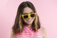 A teenage girl in sunglasses looks at camera and smiling royalty free stock image