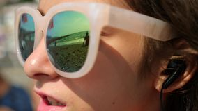 Teenage girl in sunglasses. Sits on the beach and sings a song listening to her in headphones with a smartphone. In the stock video