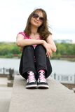 Teenage girl in sunglasses and sneakers. Sitting on the embankment Stock Photo