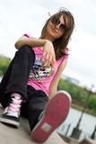 Teenage girl in sunglasses and sneakers. Sitting on the embankment Stock Image