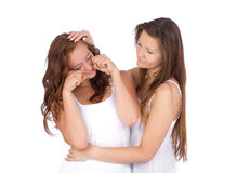 Teenage girl supporting her crying friend. On white background Stock Photography
