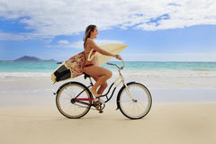 Teenage girl with surfboard and bike. Teenage girl in a red bikini wearing a flower lei riding her bicycle with surfboard on kailua beach in Hawaii looking for royalty free stock images