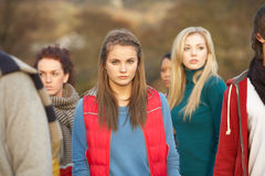 Teenage Girl Surrounded By Friends. In Outdoor Autumn Landscape Royalty Free Stock Images
