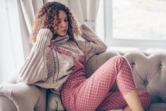 Teenage girl in sweater and jumpsuit on a couch stock images