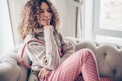 Teenage girl in sweater and jumpsuit on a couch royalty free stock photos