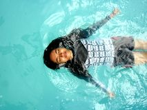 Teenage girl swimming backstroke in a pool Royalty Free Stock Photography