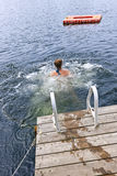 Teenage girl swimming in lake. Teen girl splashing and swimming in lake near dock Stock Photos