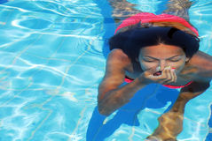 Teenage girl in the swimming pool. Teenage girl diving in the blue transparent swimming pool underwater holding breath Royalty Free Stock Photo