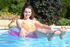 Teenage girl in swimming pool. Smiling teenage girl floating in an inflatable ring in an outdoor swimming pool Stock Images