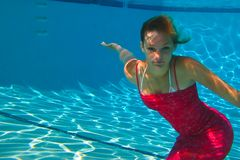Teenage girl swimming in a red dress Stock Photos