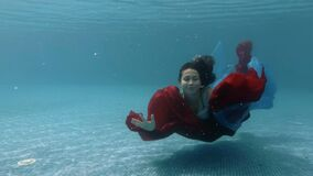 The teenage girl swims and plays with a red and blue cloth underwater at the bottom of the pool. Action camera. 4K. 29,97 fps stock footage