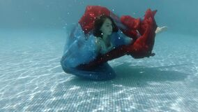 The teenage girl swims underwater in the pool in a dress and plays with a red and blue cloth. Action camera. 4K. 29,97 fps stock video
