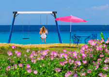 Teenage girl on a swing by the sea Stock Photos