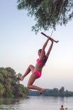 Teenage girl swinging on the rope Stock Photography