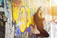 Teenage girl with tablet computer outdoors in winter. Cute happy Caucasian blonde teenage girl with tablet computer outdoors in winter against colorful graffiti Stock Images