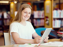 Teenage girl with tablet in library Royalty Free Stock Photo