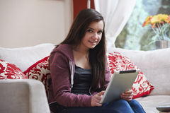 Teenage girl on tablet pc. Teenage girl using a tablet pc while sitting at home stock image