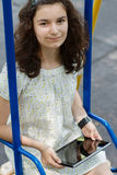 Teenage girl with tablet pc on a swing Royalty Free Stock Photos