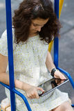 Teenage girl with tablet pc on a swing Stock Photo
