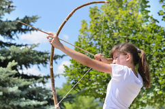 Teenage girl taking aim with a bow and arrow Royalty Free Stock Image