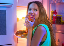 Teenage girl taking food from refrigerator at night. Portrait of beautiful teenage girl taking food from refrigerator at night Royalty Free Stock Image