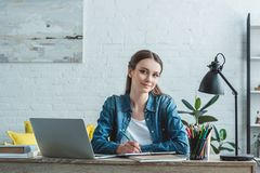 Teenage girl taking notes and smiling at camera while studying with laptop. At home stock images