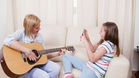 Teenage girl taking pictures of her mother playing on an acoustic guitar stock video footage