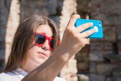 Teenage girl taking self portrait with her smart phone Royalty Free Stock Photo