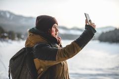 Teenage girl taking a selfie on smartphone, outdoors. In winter mountains royalty free stock image