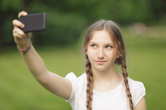 Teenage girl taking selfie on smartphone Stock Photos