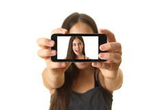 Teenage girl taking a selfie. 12 year old teenage girl taking a selfie - self portrait with her smartphone - isolated on white Stock Images