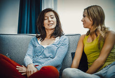 Teenage girl talking with her parent. On sofa in home stock images