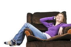 Teenage girl talking on a phone. Sitting in an armchair stock photos
