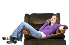 Teenage girl talking on a phone. Sitting in an armchair stock photo