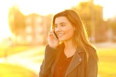Teenage girl talking on phone at sunset stock photo