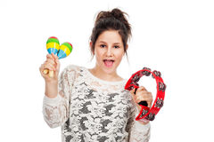 Teenage girl with tambourine and maracas. Pretty teenage girl shaking tambourine and maracas in studio on white background Royalty Free Stock Photo
