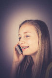 Teenage girl telephoned smiling, grain effect Stock Image
