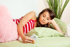 Teenage girl texting laying in bed Royalty Free Stock Images