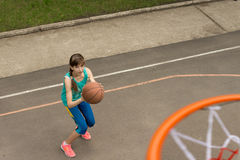 Teenage girl throwing a basketball at the net Stock Image