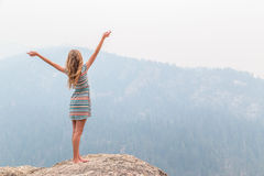 Teenage girl on top of rocky ridge Royalty Free Stock Images