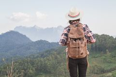 Teenage girl tourists stand and look at the beautiful mountain landscape, strolling with a relaxing backpack on top of the cliff stock images