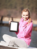 Teenage girl in tracksuit showing tablet on pier. Full length of fitness woman sport teenage girl in pink tracksuit showing blank copy space screen of tablet Royalty Free Stock Photos