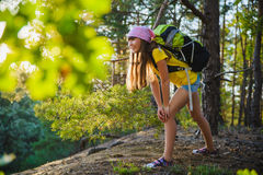 Girl traveler with backpack in hill forest. Adventure, travel, tourism concept Stock Image