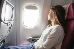 Teenage girl travelling by airplane stock photography