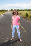A teenage girl travels barefoot on an empty road Stock Photo