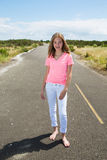 A teenage girl travels barefoot on an empty road Royalty Free Stock Photo