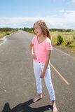 A teenage girl travels barefoot on an empty road Stock Photography